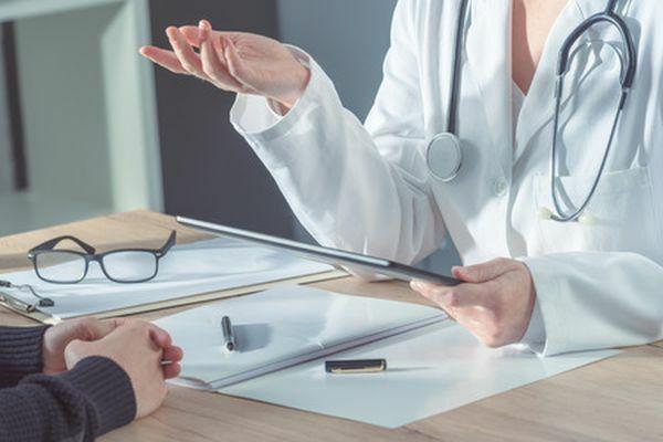 Huisarts en patiënt in gesprek, tafel en handen zichtbaar 123rtf 600 - 400